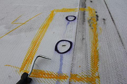 Zur Reparatur werden schadhafte Stellen auf einem Flachdach markiert.
